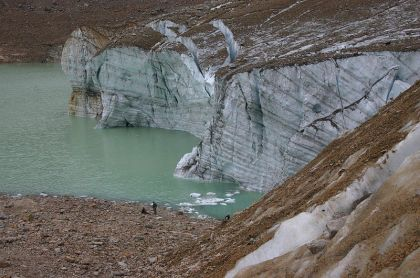 The margin of a large glacier ending in a metlwater pond. The ice and surrounding ground are covered with gravel and sand.