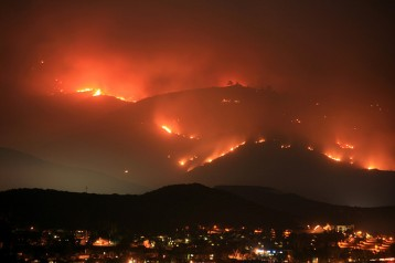 A mountain on fire at night, with a city in the valley.