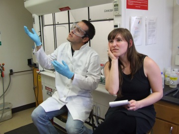A young white man wearing a lab coat, gloves and goggles is busily explaining science to a young white female with a notepad who looks bored and discouraged. The conversation is taking place in a lab.