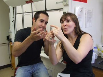 A young white man is enthusiastically describing something to a young white women, who is very interested. Both are wearing casual attire, in a lab.